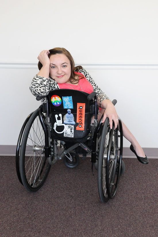 White woman with brown hair and fabulous clothes turned around, to face the camera with the back of the multi-colored wheelchair